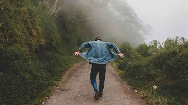 person wearing blue denim jacket while walking on foggy road