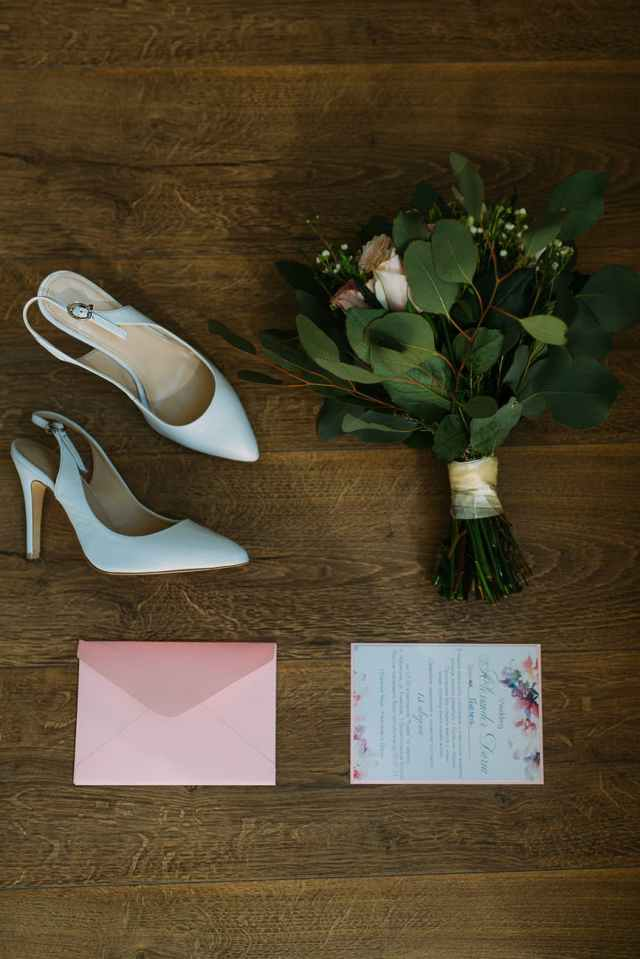 pair of white leather pointed toe slingback shoes beside bouquet of flowers