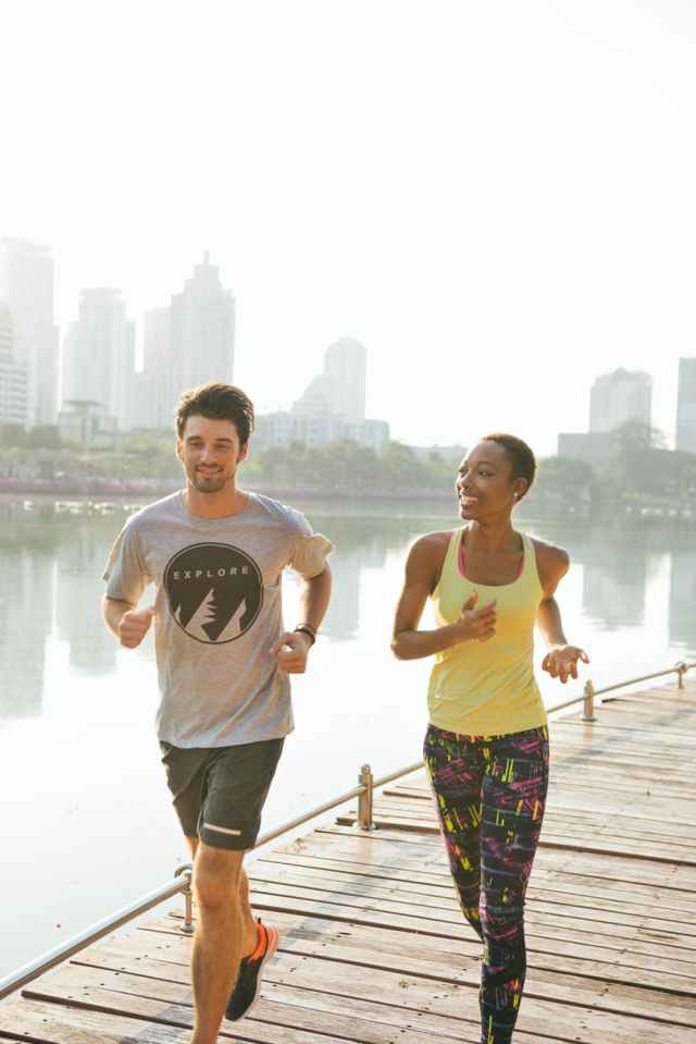 man and woman jogging near body of water