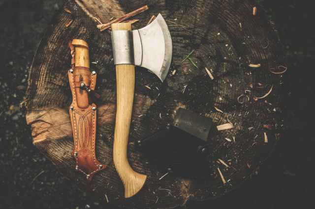 brown wooden axe besides brown leather knife holster