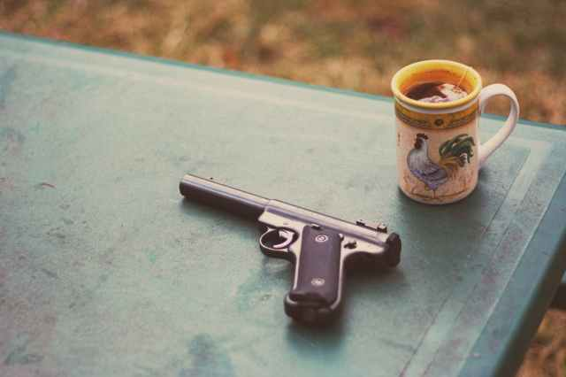 photo of handgun near mug