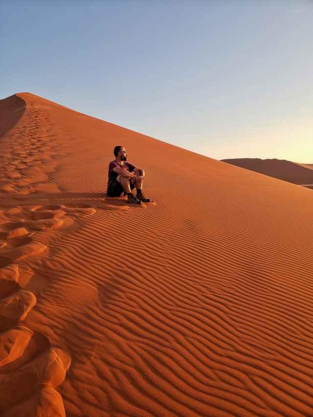 man sitting on desert