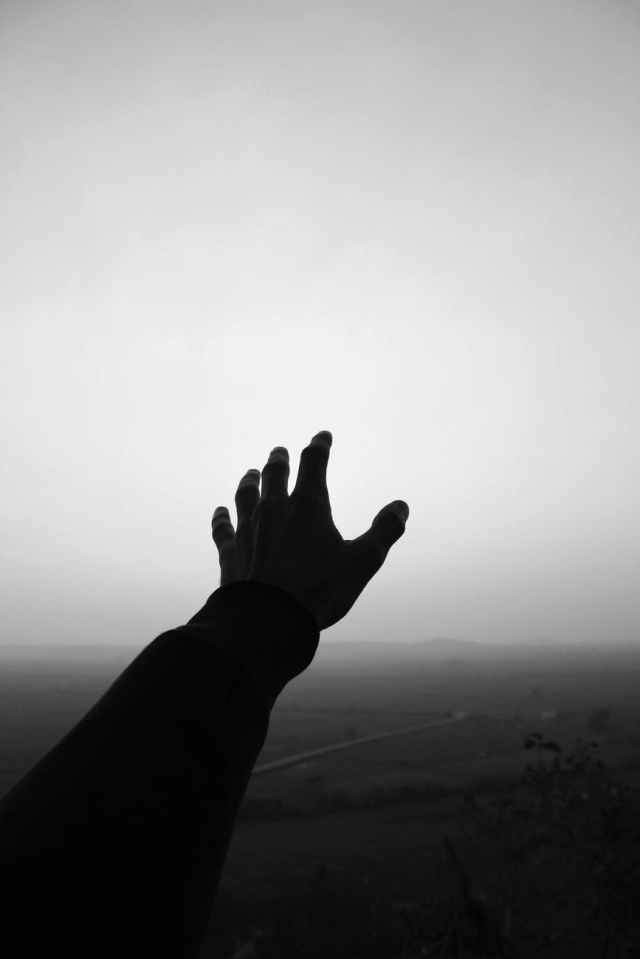 grayscale photo of person s hand reaching for the sky
