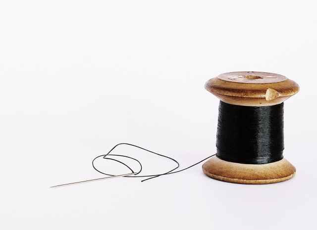 black thread on a wooden spool