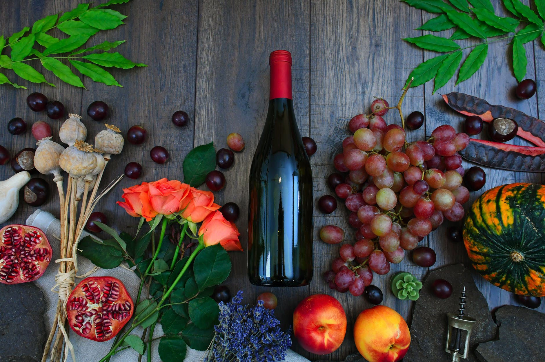 wine bottle beside grapes roses and several fruits on brown wooden surface