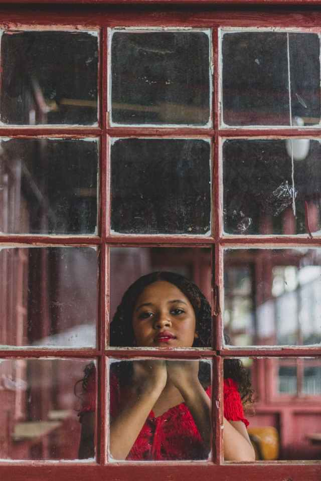 woman in front of red glass window