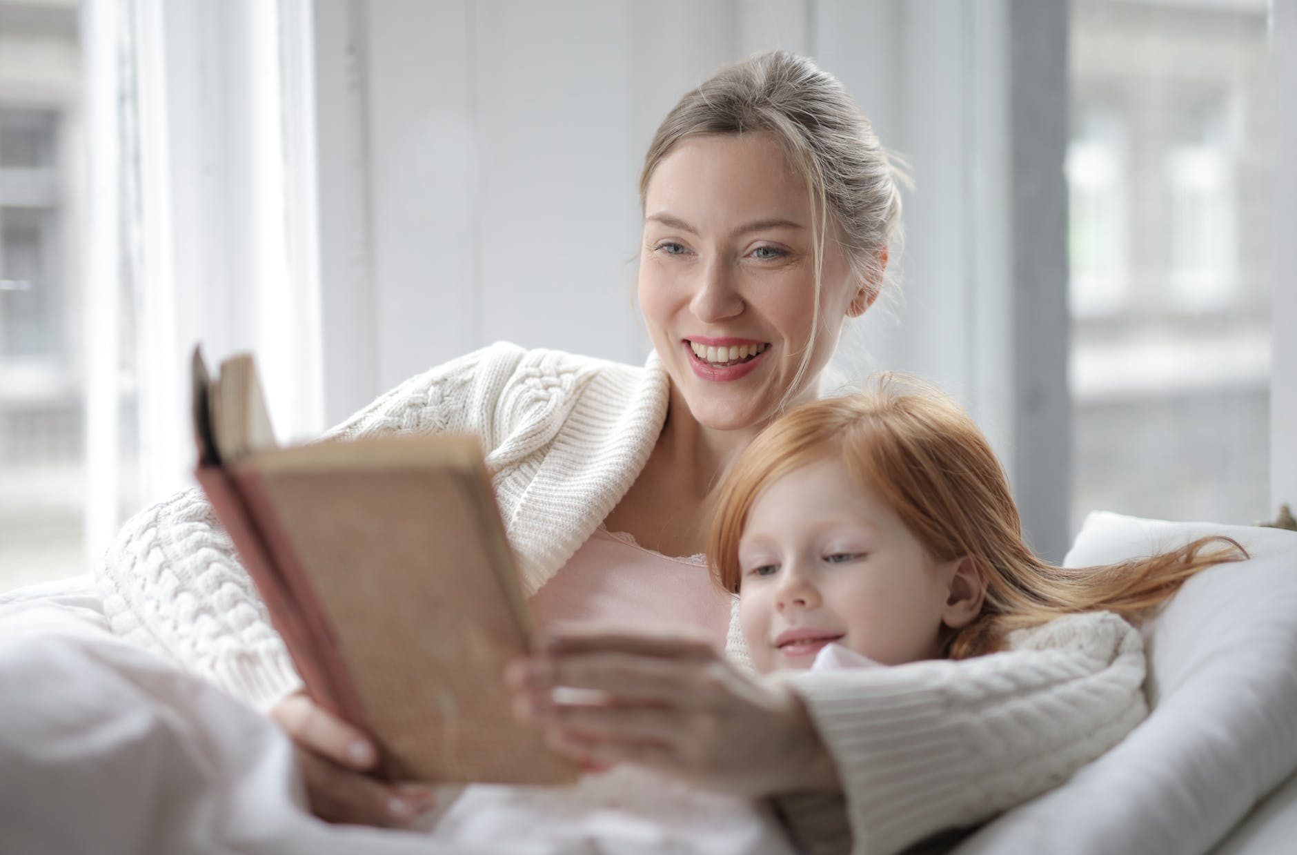 woman holding book lying on bed beside girl