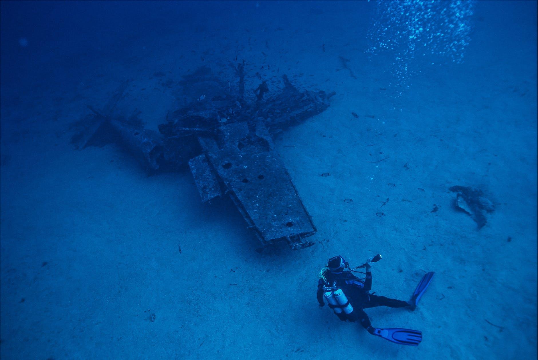 photo of person scuba diving near wreckage
