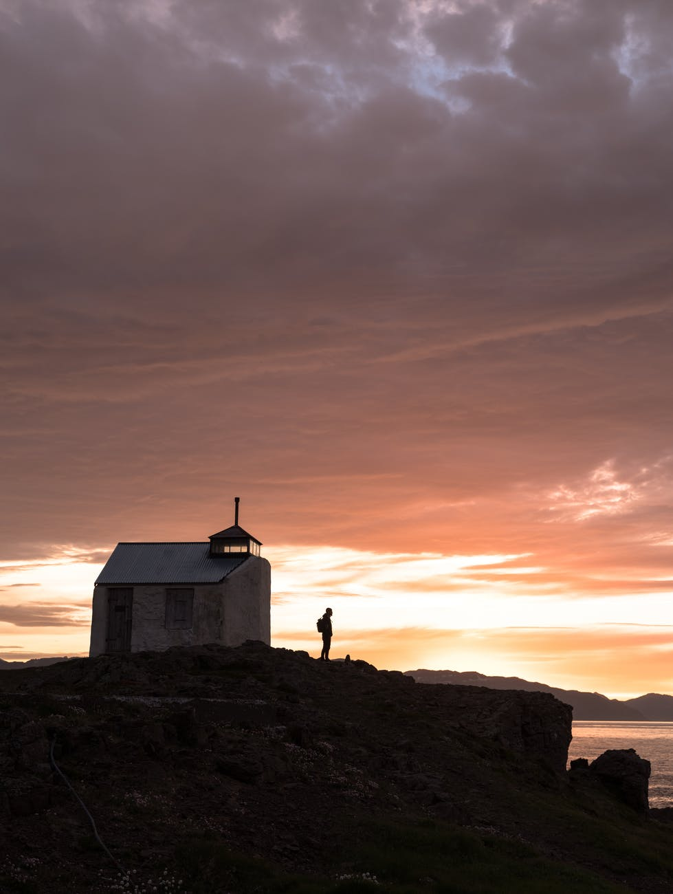 remote house and silhouette on rocky seashore