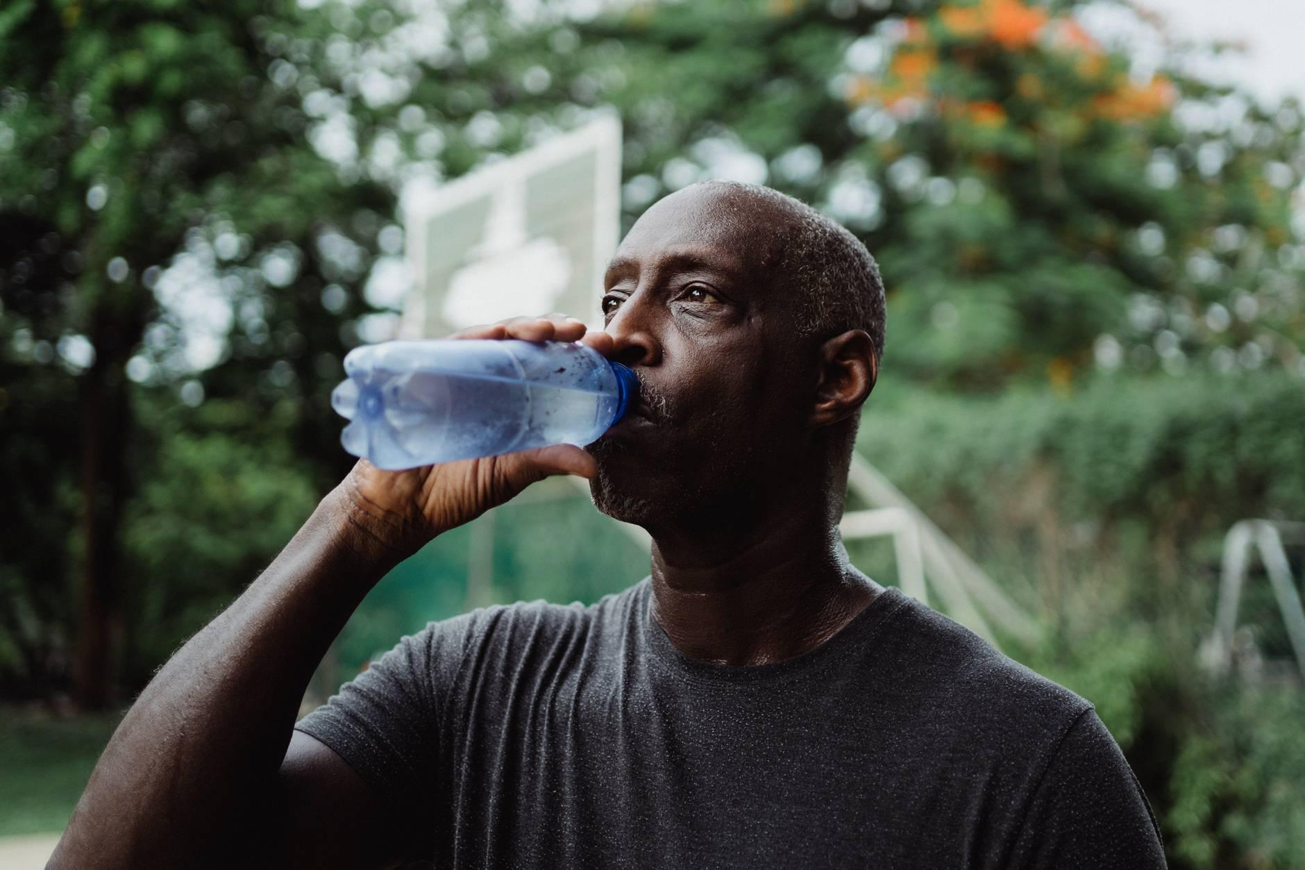 man in gray crew neck shirt drinking water