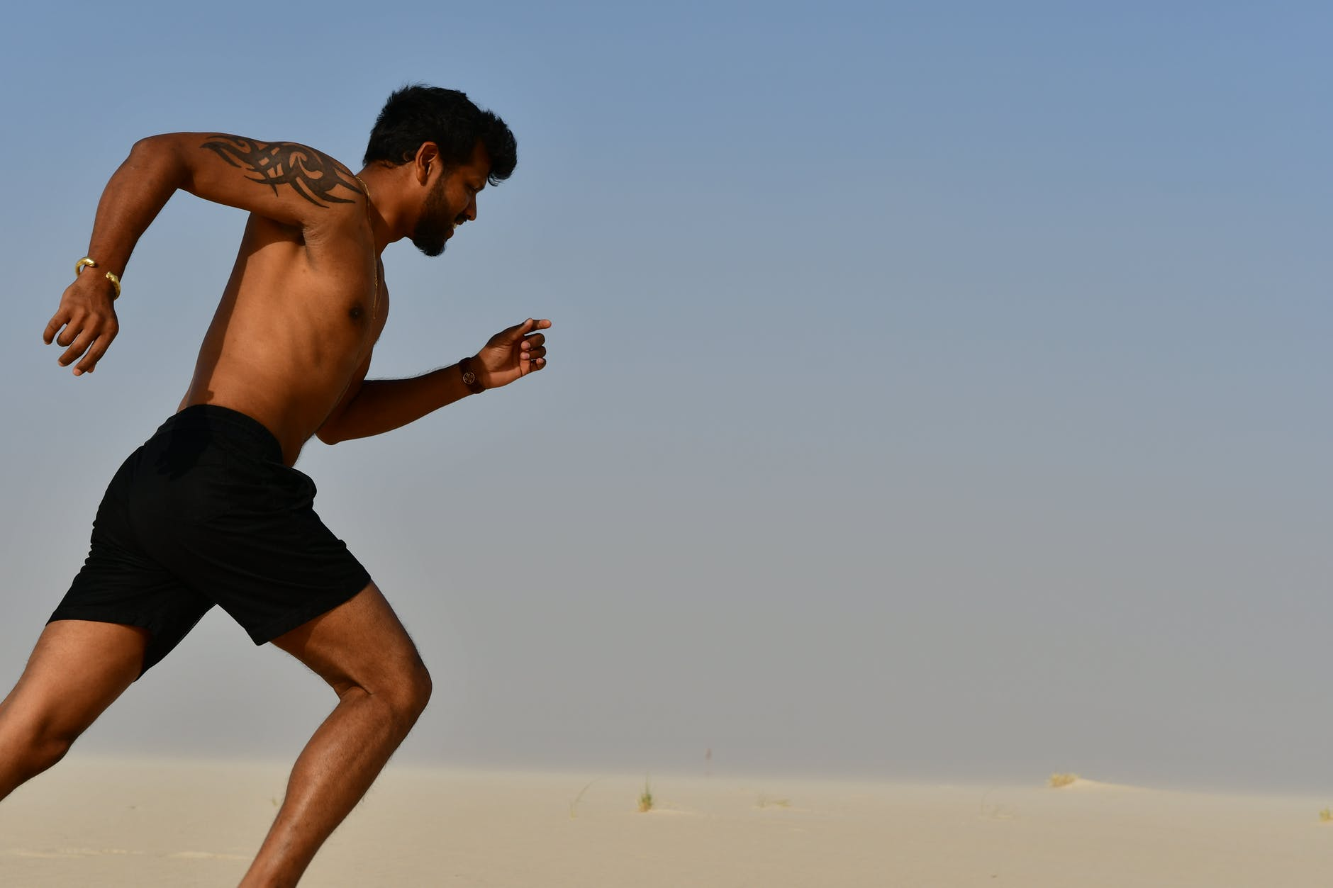 strong shirtless sportsman jogging on bright day